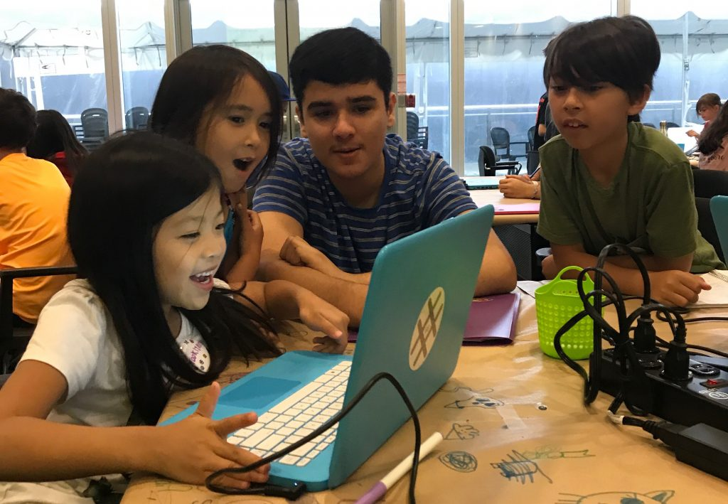 Campers solving a problem with their code with the help of their mentor
