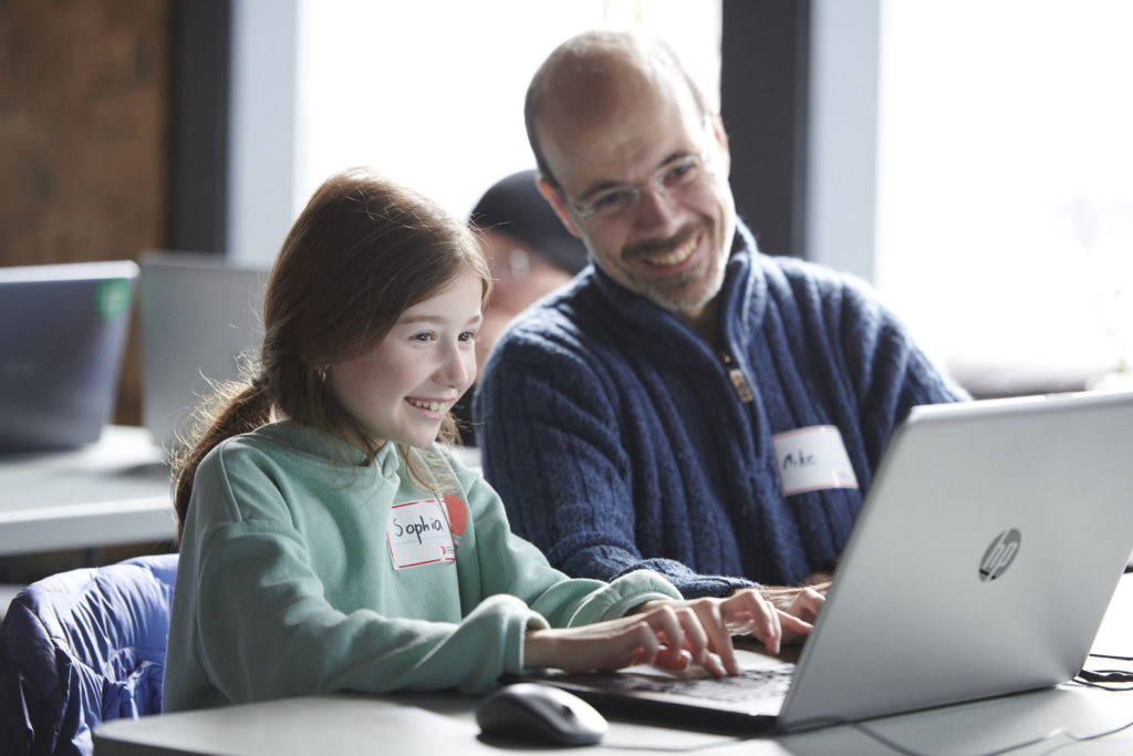 Young girl typing on the computer, she is excited, her dad is sitting with her and looking at the screen