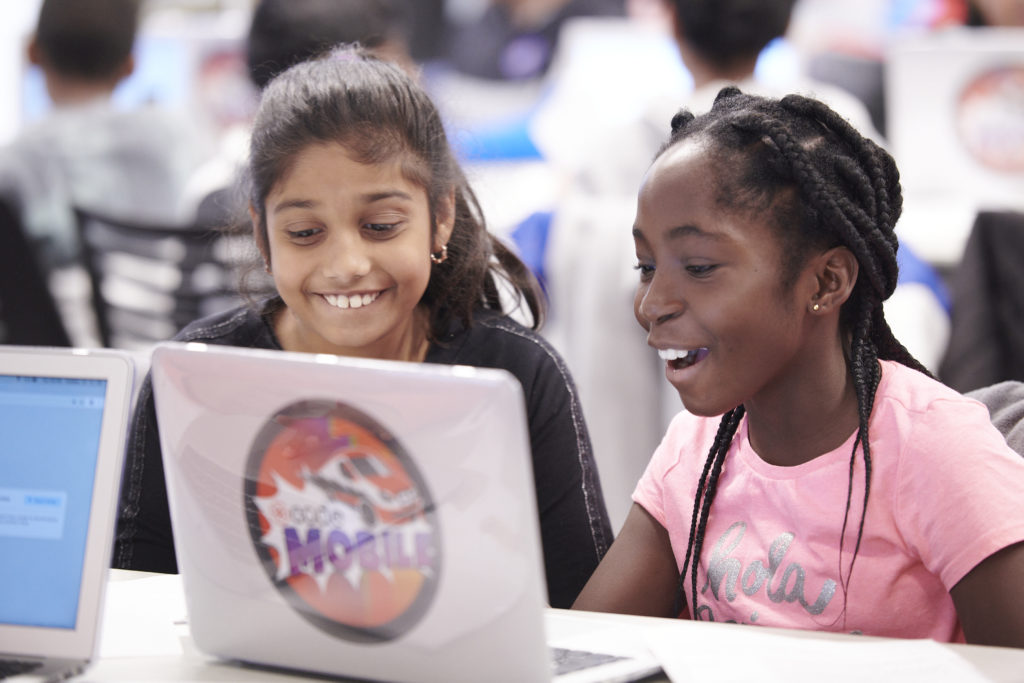 Two girls are sitting  and smiling in front of laptop