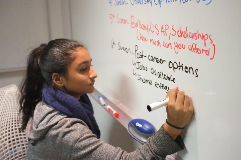 Ten girl is writing on a blackboard