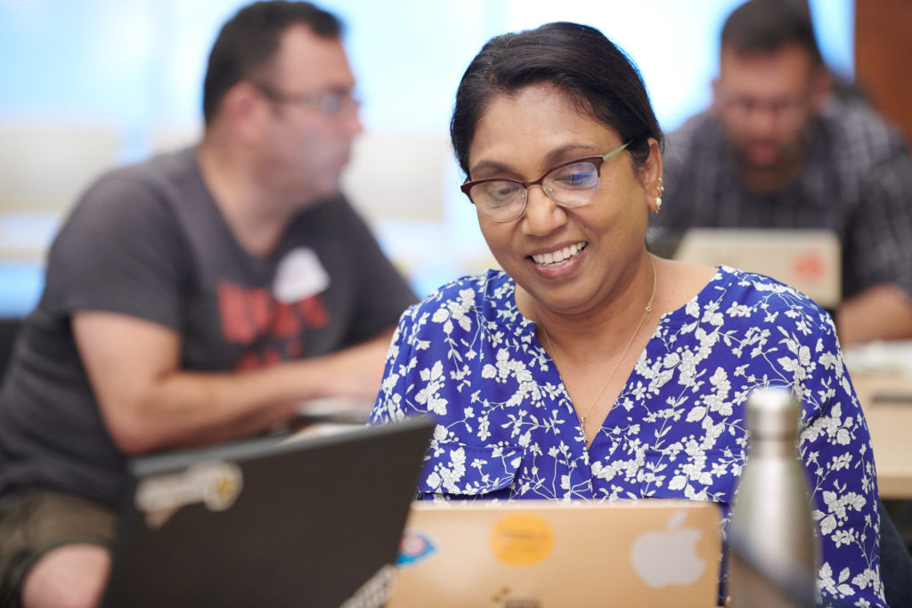 Female-identified person looking at their laptop and smiling