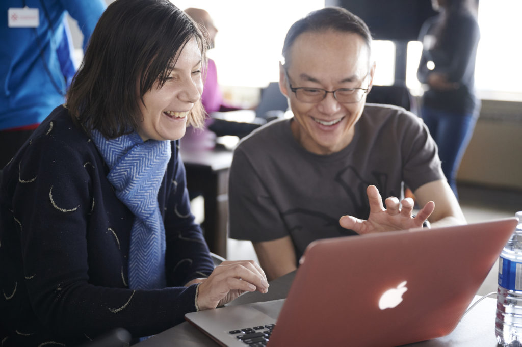 Two adult learners smiling and learning on a laptop