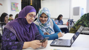 two women coding together