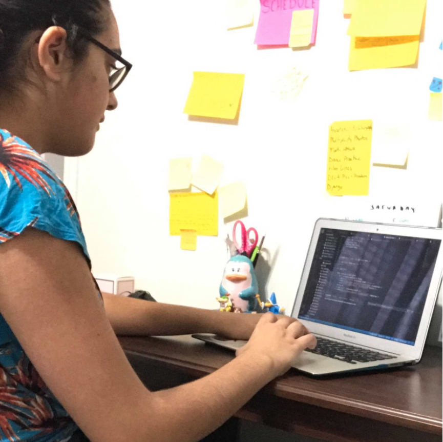 Teen girl coding on her laptop