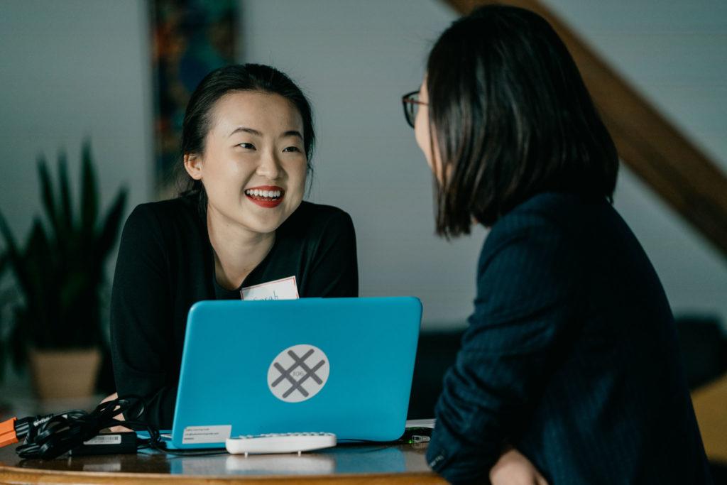 Two women talking by a laptop
