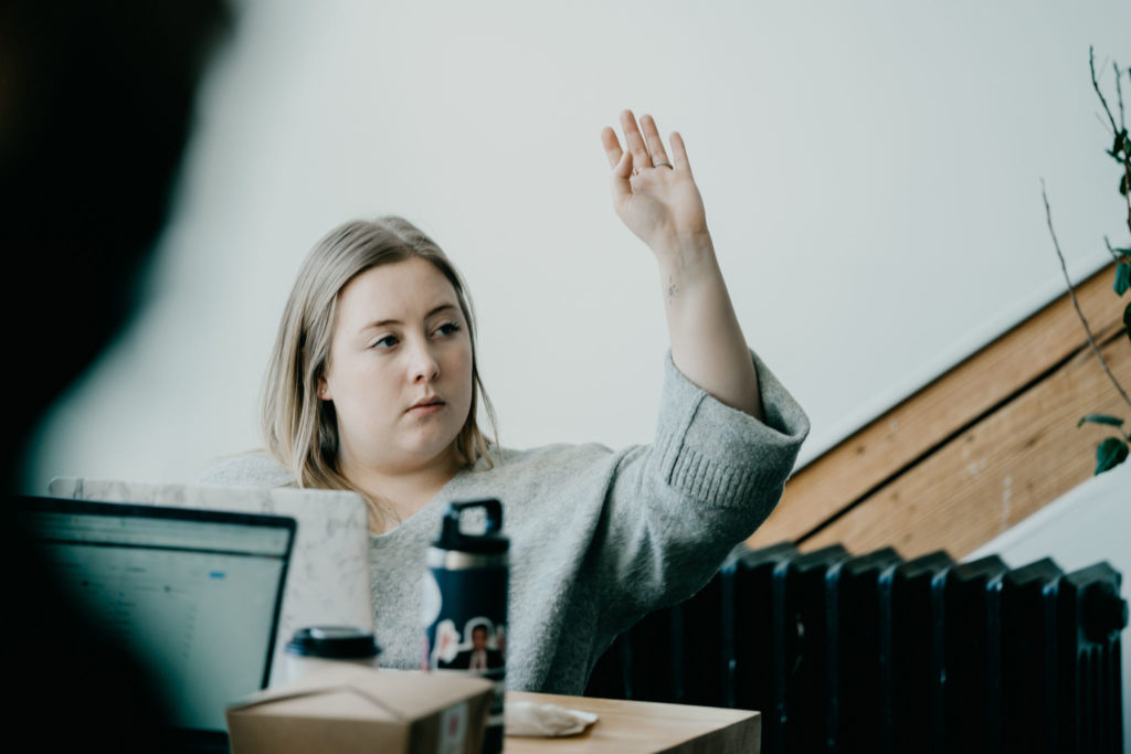 Female-identified participant raising their hand