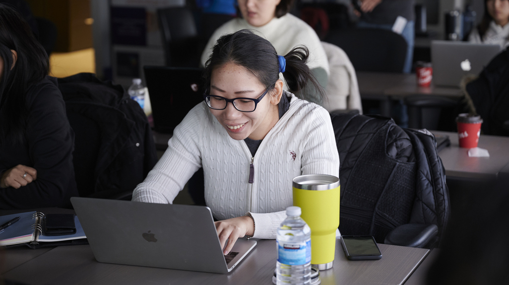 Woman coding on laptop in class
