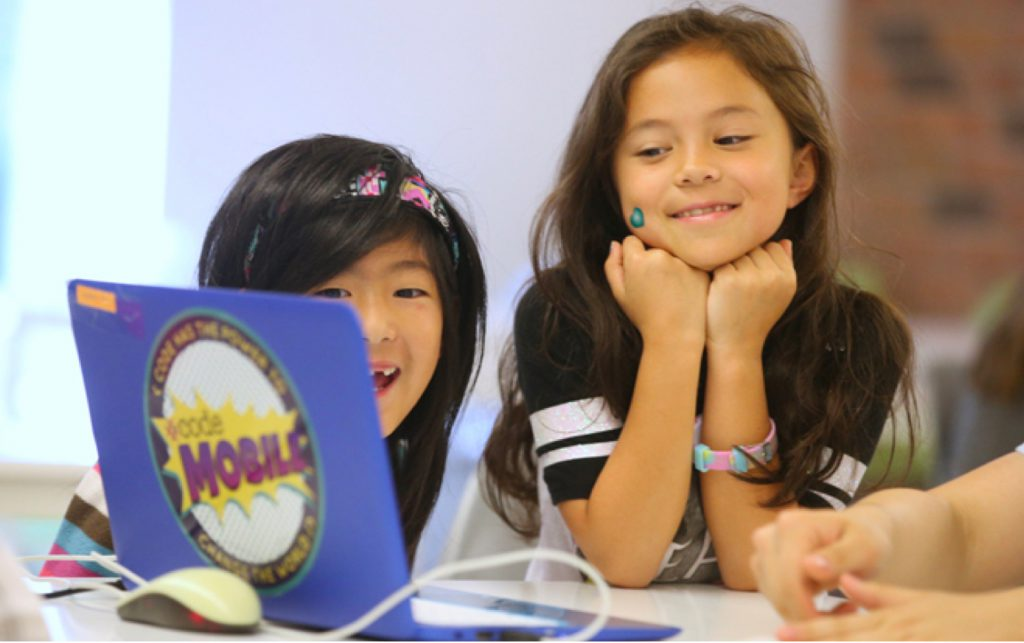 two girls looking and smiling at a code mobile laptop